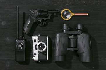 Portable radio, handgun, binoculars, magnifying glass and photo camera on a black flatlay detective table background. Interrogation. Surveillance.