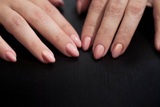 Nude manicure with gold decor. Womens hands close up