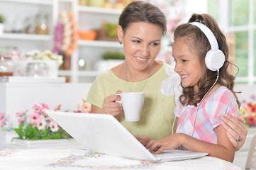 Portrait of happy mother and daughter using laptop together
