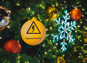Electric warning sign hang on Christmas tree with light bokeh background