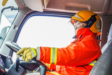 Portrait of confident mature fireman driving firetruck with communication interior view at station