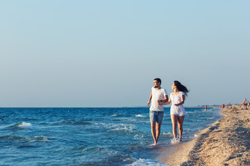 man and woman happily run along the coastline of the sea.