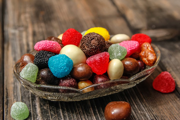 Different candies in a crystal bowl on old wooden table. Multi colored gummy candy coated with sugar, chocolate and fruit candy.