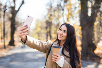 Young woman with takeaway coffee making selfie in the autumn park.