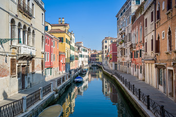 Sunny view of empty channel and street of Venice old town.