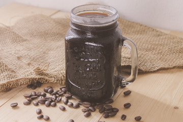 Cold Brew Black Ice coffee in a Mason jar and coffee beans on a wooden table. Vintage Tone
