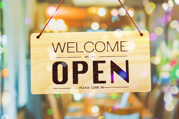 A business sign that says open on cafe or restaurant hang on door at entrance. Wall mural