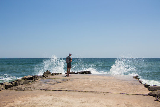 Young boy alone on a pier and waves crash on the rock