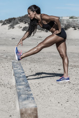 Black woman warming up near beach