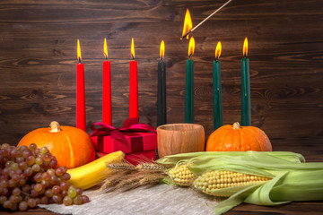 ignition of Kwanzaa traditional candles, holiday concept with gift box, pumpkins, ears of wheat, grapes, corns, banana, bowl and fruits on wooden background, close up