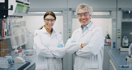 Portrait of two smiling scientists wearing protection glasses satisfied with a great results of completed research in laboratory. Concept: research,biochemistry, pharmaceutical medicine
