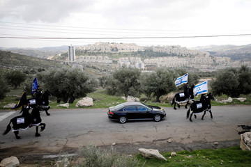 The convoy of Pierbattista Pizzaballa, the acting Latin Patriarch of Jerusalem, is escorted by mounted Israeli policemen in Jerusalem, as the Jewish settlement of Har Homa is seen in the background, before his crossing into Bethlehem