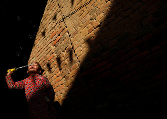 Light illuminates a girl as she blows bubbles along the alley in Lalitpur