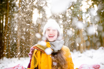 Portrait of a young exccited woman dressed in bright winter clothes enjoying snow falling in pine forest