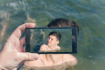 Female taking a picture of a boy on the beach on the phone. Teen boy swimming in sea waves with water splashes. Travel and family concept