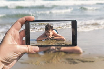 Female taking a picture of a boy on the beach on the phone. Teen boy jumping in sea waves with water splashes. Travel and family concept