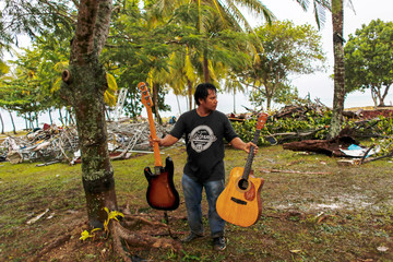 A worker holds guitars belonging to a rock band Seventeen at a resort which was hit by a tsunami in Tanjung Lesung