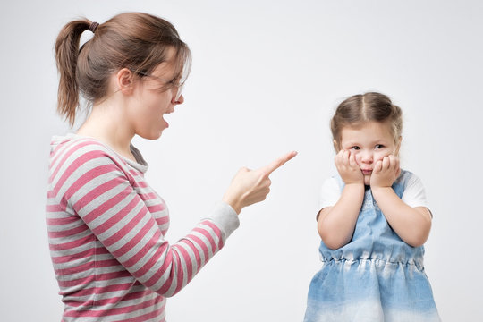 Young mother scold her daughter. Little girl covering her face with hands. Problems between parents and their children.