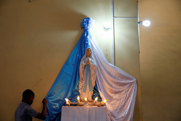 A man decorates a statue of the madonna during Christmas day preparations at the Saint Benoit church in Kinshasa