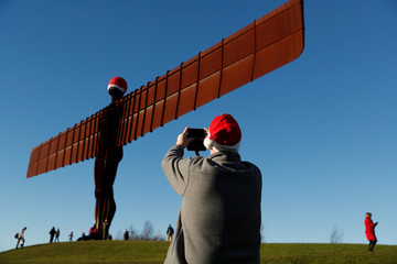 Passerby takes pictures of the Angel of the North statue adorned with Santa Claus' hat in Gateshead