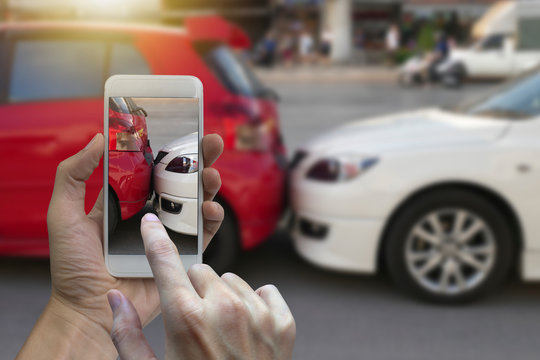 Close up hand holding smartphone and take photo at The scene of a car crash and accident, car accident for car insuranc claim