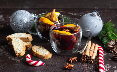 Glass cups of hot mulled wine or gluhwein with spices and orange pieces on dark brown background. Christmas mulled wine. Traditional drink on winter holiday. Copy space.