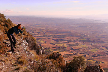 GIRL TAKING PHOTOS OF A GREAT VALLEY FROM THE SUMMIT OF A MOUNTAIN