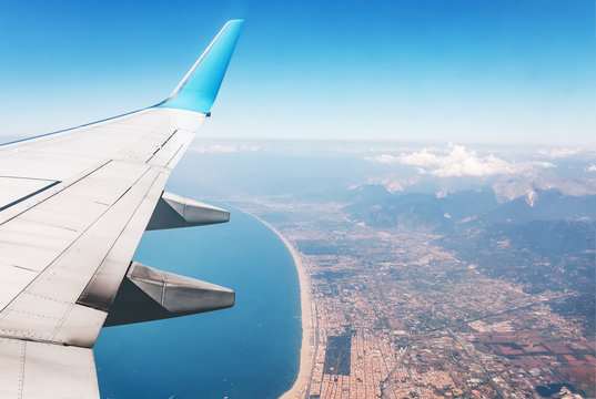 Airplane wing with mediterranean sea and big city with mountains