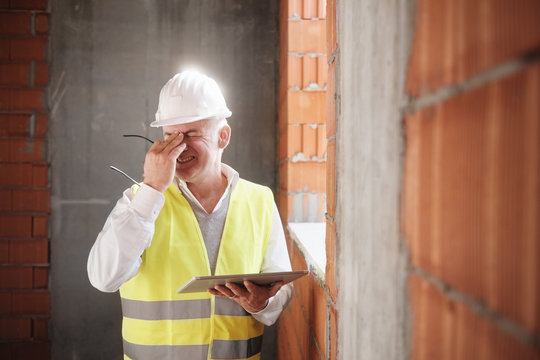 Engineer With Headache At Work With Computer In Construction Site