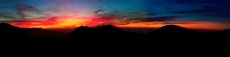 contrasting sunset high in the mountains panorama