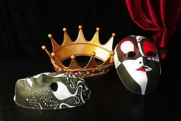 Gold crown and masquerade masks against black background