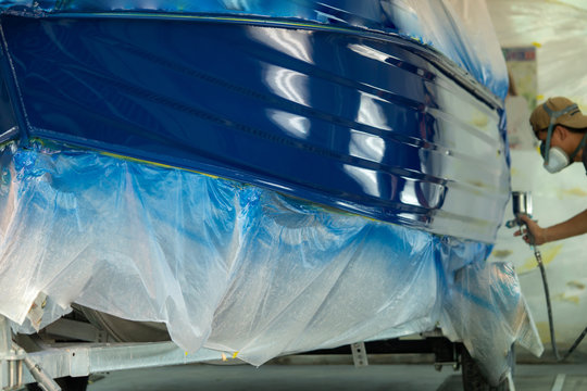spray gun with paint for painting a boat