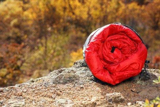 Red sleeping bag on rock outdoors, space for text. Camping equipment