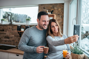 Smiling young couple taking selfie in the morning at home.