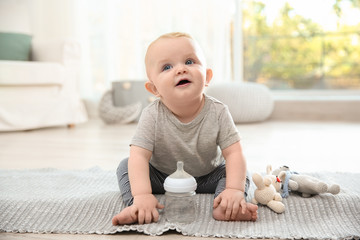 Cute baby with bottle sitting on floor in room