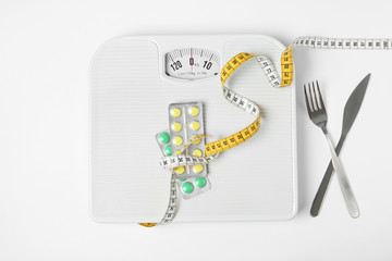 Scales with weight loss pills and measuring tape near cutlery on white background, top view