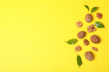 Flat lay composition with walnuts and space for text on color background