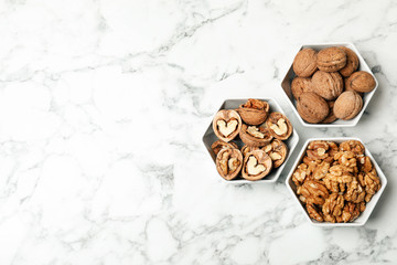 Flat lay composition with walnuts and space for text on marble background