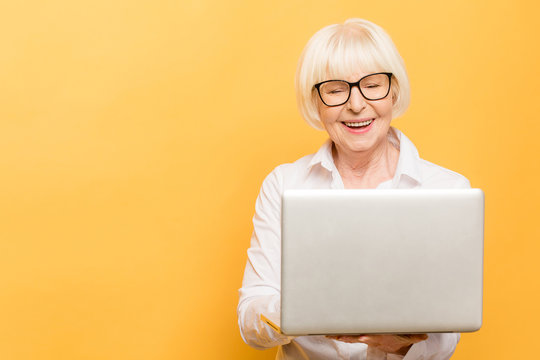 Senior business woman with laptop. Isolated over yellow background.
