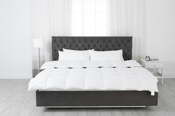 Large comfortable bed in light room. Stylish interior