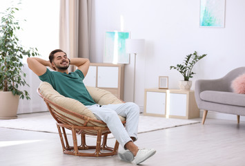 Handsome young man sitting in armchair at home. Space for text