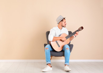 Handsome young man with guitar in armchair near color wall indoors. Space for text