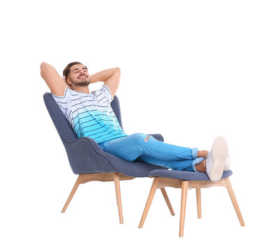 Handsome young man relaxing in armchair with legs on footrest against white background