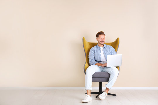 Handsome young man with laptop in armchair near color wall indoors. Space for text