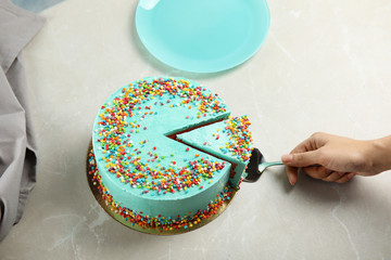 Woman taking slice of fresh delicious birthday cake at table, closeup