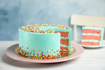 Cut fresh delicious birthday cake on table