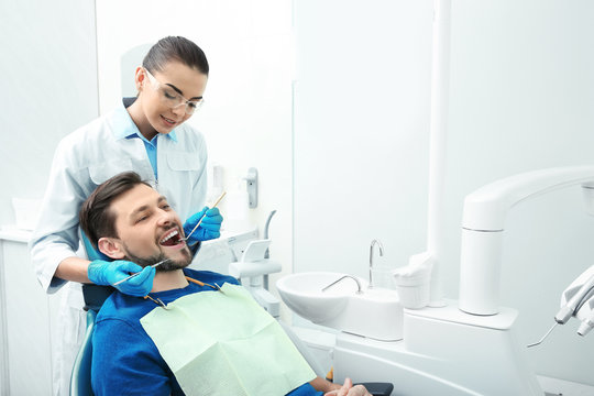 Professional dentist working with patient in modern clinic. Space for text