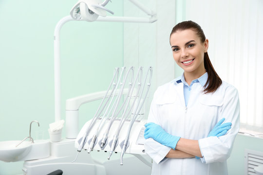 Young female dentist in white coat at workplace. Space for text