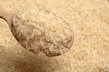 Parboiled rice in wooden spoon, closeup view
