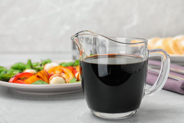 Balsamic vinegar in glass jug near plate with salad on table